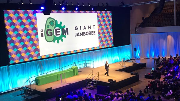 iGEM Jamboree attendee on stage talks to a crowd of young scientists