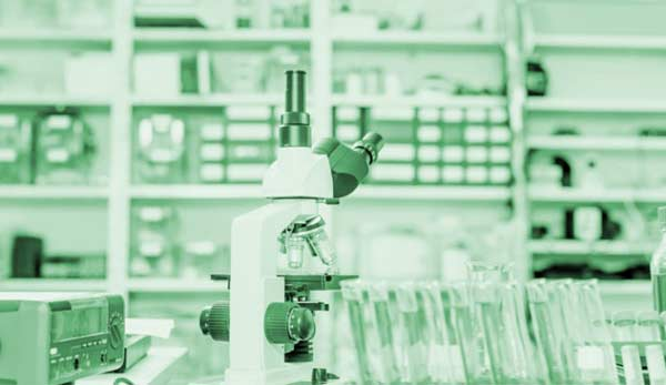 A microscope stands on a laboratory counter