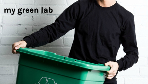 A man in a black shirt holds a green recycling bin